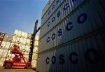 Shanghai port loading dock with forklift moving shipping containers of the China Overseas Shipping Company (COSCO)