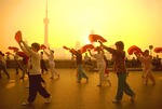 Shanghai Bund morning exercise team with fans, Pudong skyline in background