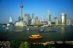 Shanghai's Pudong skyline across the Huangpu River from The Bund, barges and tourist boat on river