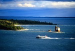 Mackinac Island ferry from Mackinac City passing Round Island Lighthouse in Straits of Mackinac with Lake Huron in distance