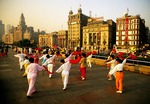 Shanghai Bund morning exercise group with buildings from 1930's in background