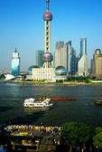 Shanghai's Pudong skyline with Oriental Pearl TV Tower across the Huangpu River from The Bund, barges and tourist boat on river