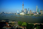 Shanghai's Pudong skyline across the Huangpu River from The Bund, barges on river