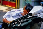 Nanjing man reading newspaper in pedicab on street