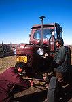 Mongolian farm boys working on Soviet era tractor on the grasslands in NE Inner Mongolia