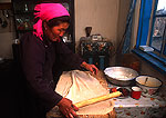 Mongolian farm wife making bread in kitchen on dairy farm on the grasslands in NE Inner Mongolia