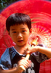 Girl at Hangzhou's Lingyin Temple twirling colorful umbrella