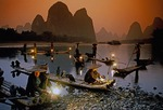 Li River cormorant fishermen at dusk lighting lanterns on their bamboo rafts near Xingping (Guilin area)