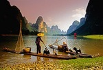 Li River cormorant fishermen on bamboo rafts watching sail boat near Yangshuo/Xingping (Guilin area)