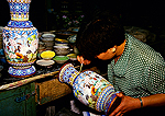 Beijing cloisonne workshop with woman artisan decorating vase