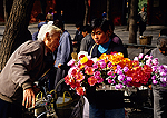 Beijing flower seller with elderly customer at a street market