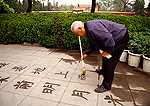 Beijing's Jingshan Park, elderly man practicing calligraphy with brush and water on sidewalk in early morning  