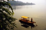 Hangzhou's West Lake in early morning summer mist with boat