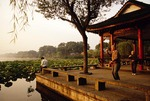 Hangzhou's West Lake with elderly couple doing morning tai chi (tai chi chuan, tai ji quan) exercises