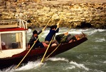 "Daning River boatman poling boat upstream on the tributary of the Yangtze in the ""Little Three Gorges"""