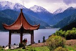 Xinjiang's Heavenly Lake (Tian Chi) in the Tian Shan Mountains with tourists on viewing pavilion