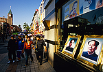 Beijing's Wanfujing shopping mall with teens passing portraits of Zhou Enlai and Mao Zedong in shop window