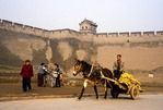 Pingyao's rammed-earth ancient wall of 2,700-year-old city, with local farmer on donkey cart