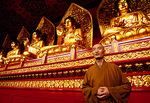 Buddhist monk in Bailin Temple's 10,000 Buddha Hall, one of the world's largest.