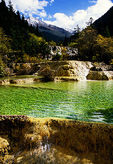 Travertine pool below Liantai Waterfall with Huanglong Peak at top in the Huanglong (Yellow Dragon) natural scenic area