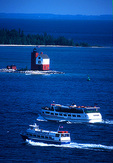Mackinac Island ferries passing Round Island light house with Lake Huron in distance