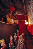 Rajasthani puppeteer entertaining in hotel courtyard for tourists