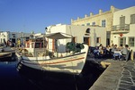 Paros taverna next to a fishing boat in the inner harbor of the town of Naoussa
