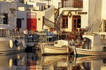 Paros fishing boats docked next to tavernas on the inner harbor of the town of Naoussa