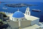 Santorini's Greek Orthodox Church of Kimis Theotokov with cruise ships anchored below in volcano caldera
