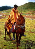 Basotho horseman wearing mohair blanket on high mountain plateau near Sani Pass