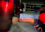 Bangkok Muay Thai (Thai Kick Boxing) training camp; boxer kicking bag