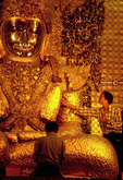 Mandalay's Maha Muni (Great Sage) Buddha with men applying gold leaf
