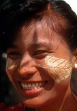 Thanaka-bark makeup in leaf design on young woman's cheeks.