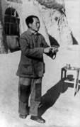 """Builder of a New Cause,"" Mao Zedong, 1942, in patched trousers before his cave home in Yenan, giving a report to cadres"