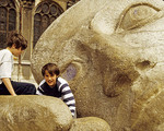 Parisian boys playing on sculptured head, L'Ecoute, by Henri de Miller, located in front of Saint Eustache church