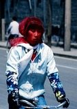 Beijng woman bicyclist wearing sheer scarf over face for protection from early spring dust storm
