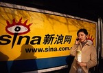 Beijing woman using cell phone next to billboard ad for Internet provider Sina.com