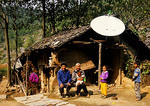 Farm family in front of satellite TV dish equipped house in poor mountain village