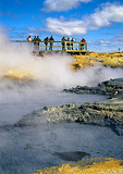 Icelandic geothermal field at Namaskard Thermal Area with tourists viewing from boardwalk