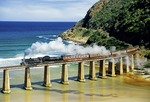 Outeniqua Choo Tjoe steam train crossing tressel at mouth of Kaimans River on Indian Ocean near Wilderness in South Africa's Western Cape