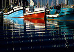 Reflections of fishing boats in Hout Bay Harbor, Western Cape, South Africa