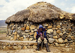 Basotho man at top of Sani Pass next to stone rondavel house in the Drakensberg mountains in Lesotho