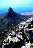 Thrill seekers rapelling down rock cliff of Table Mountain with Lions Head and Cape Town South Africa in background