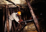 Mine worker in gold mine using jack hammer at Gold Reef City