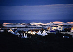 Houses and sand dunes at dusk on Indian Ocean shore at Arniston