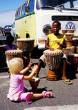 South African children playing bongo drums in oceanside parking lot in Hermanus