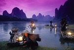 Li River cormorant fishermen on bamboo rafts lighting lanterns at dusk at Xingping