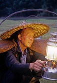 Li River cormorant fisherman lighting lantern at dusk on his bamboo raft at Xingping