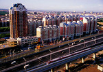 Beijing's eastern suburb of Tongzhou with high rise condominium apartments and toll highway and commuter train into city