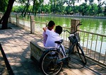 Beijing Back Lakes area couple on park bench along Qianhai Lake